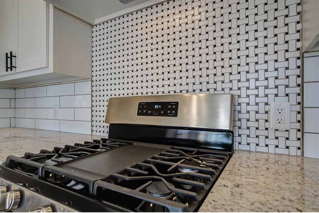 Detail of gas stove and backsplash in kitchen on new home for sale.