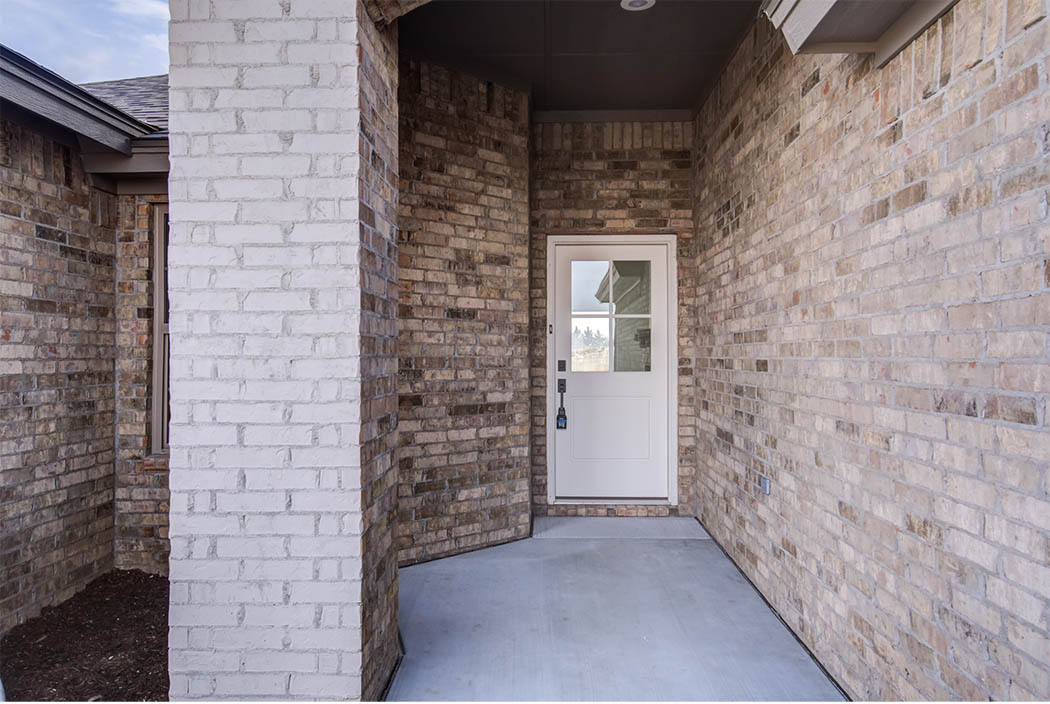 Entry sidewalk and front door of home for sale in Lubbock, Texas.