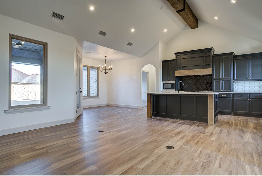 Living area in home for sale in Lubbock featuring vaulted ceiling and fireplace.