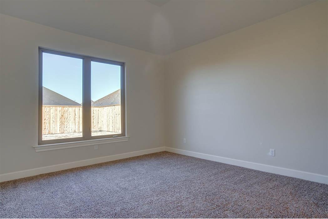 Bedroom in new home in Lubbock, Texas by Sharkey Custom Homes.