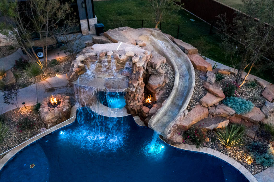 Dramatic lighting in outdoor pool area, featuring a waterfall in custome home near Lubbock.