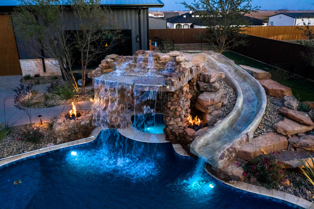 Evening lighting throughout swimming pool in custom home's back yard.