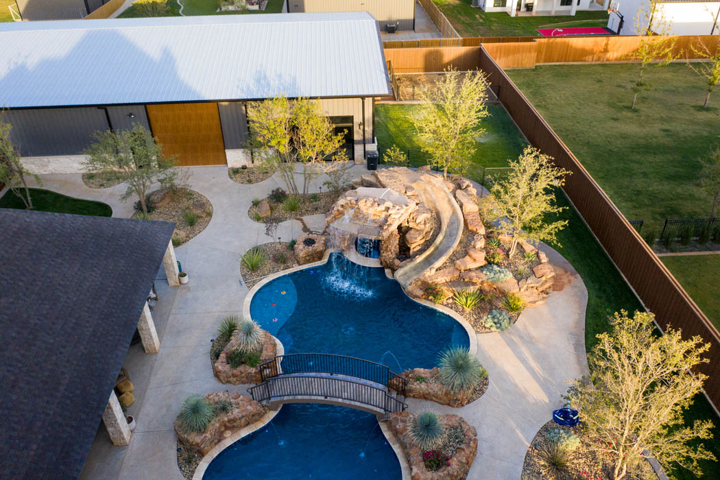 Aerial view of back yard space with swimming pool and outbuilding.