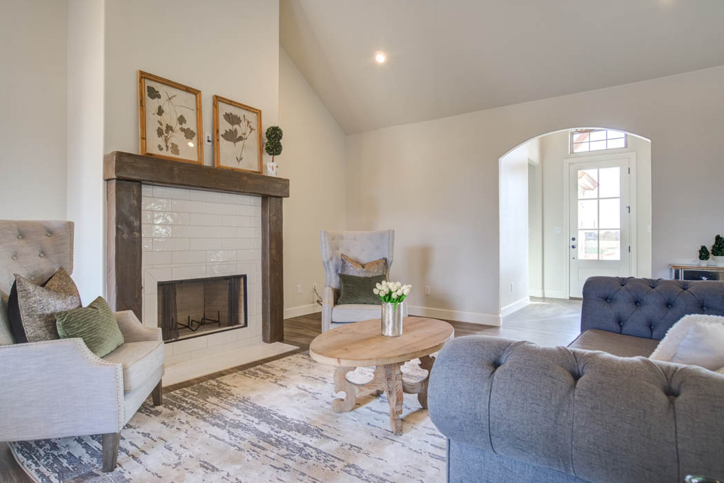 Spacious living area with cozy fireplace in new home for sale in Lubbock, Texas.