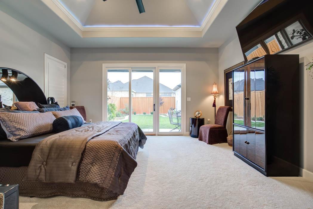 Spacious master bedroom with patio doors, in custom home in Lubbock, Texas.