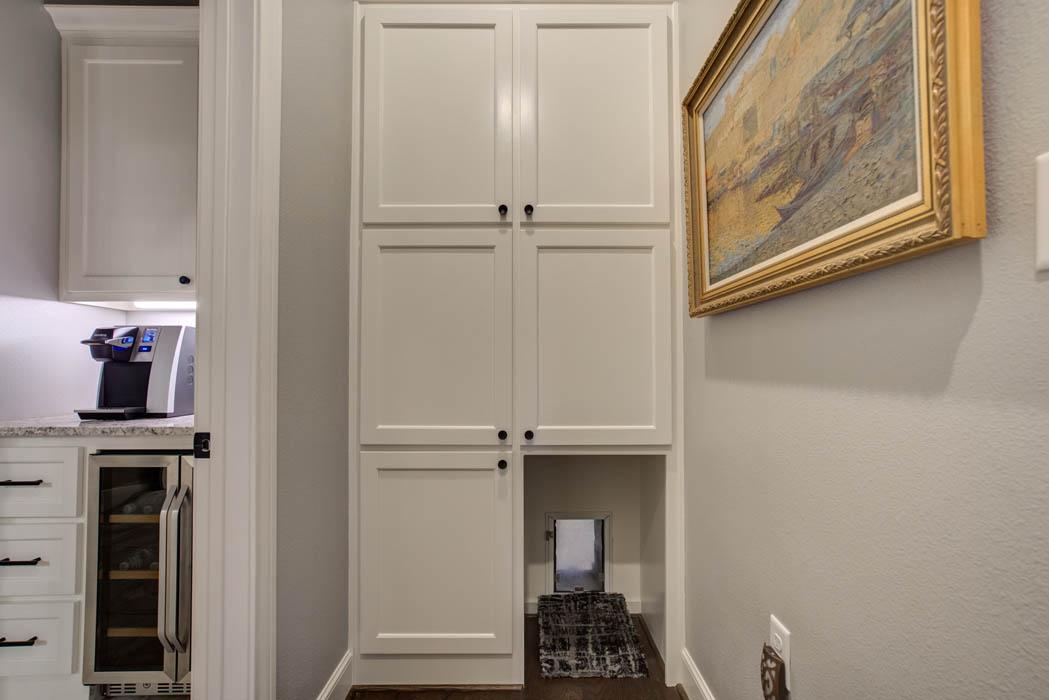 Wine bar service area with special pet door, adjacent to master bedroom in custom home.