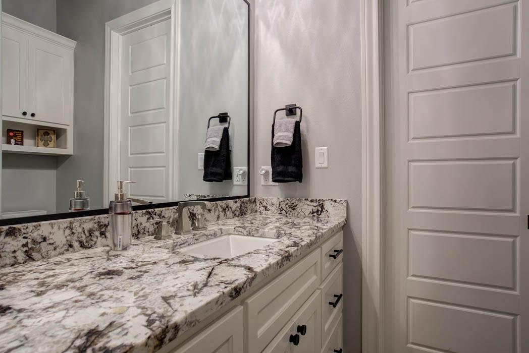 Stone vanity in secondary bath of custom home.