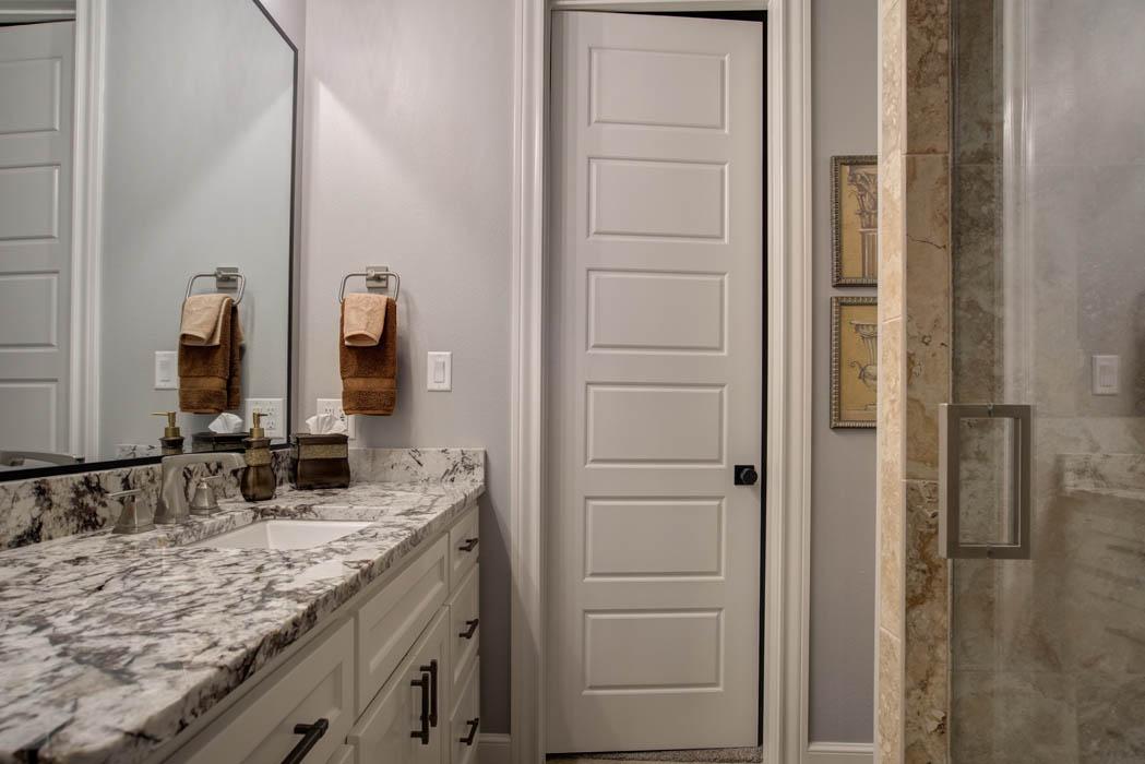 Stone vanity in secondary bath of beautiful custom home.