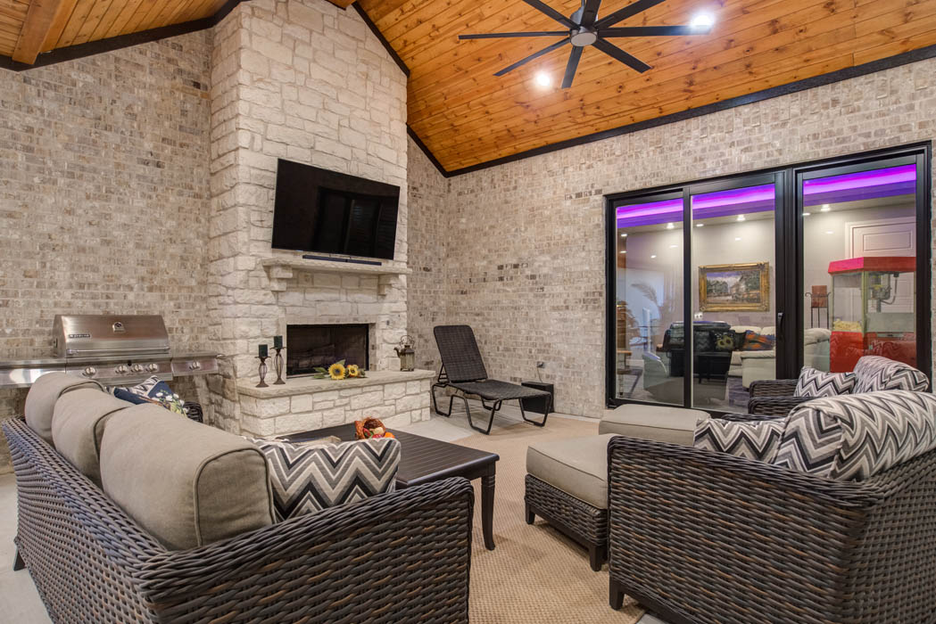 Outdoor covered patio area with fireplace and TV.
