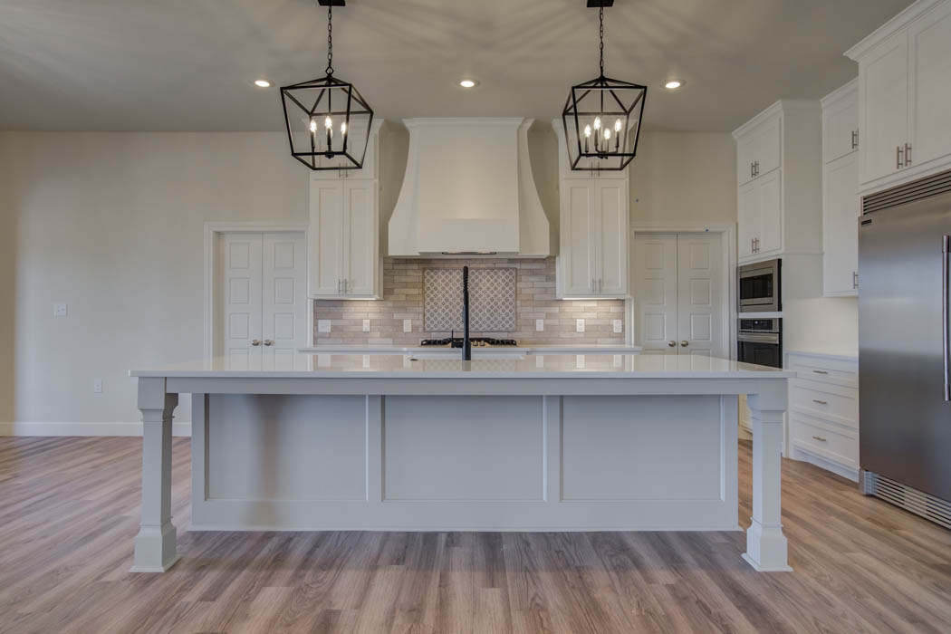 View of kitchen and bar counter in new house for sale by Sharkey Custom Homes.