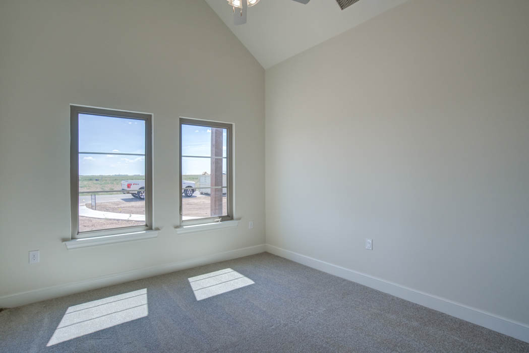 Spacious bedroom in Lubbock area home with vaulted ceiling.