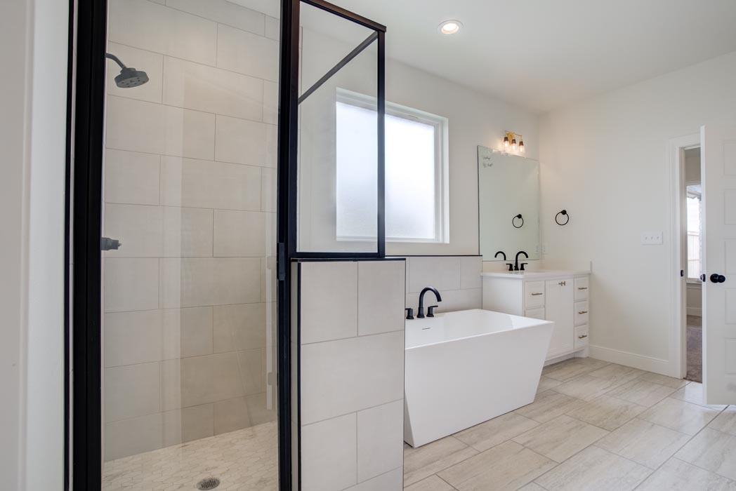 Example of spacious master bath with glass shower in new home built by Sharkey Custom Homes in Lubbock, Texas.