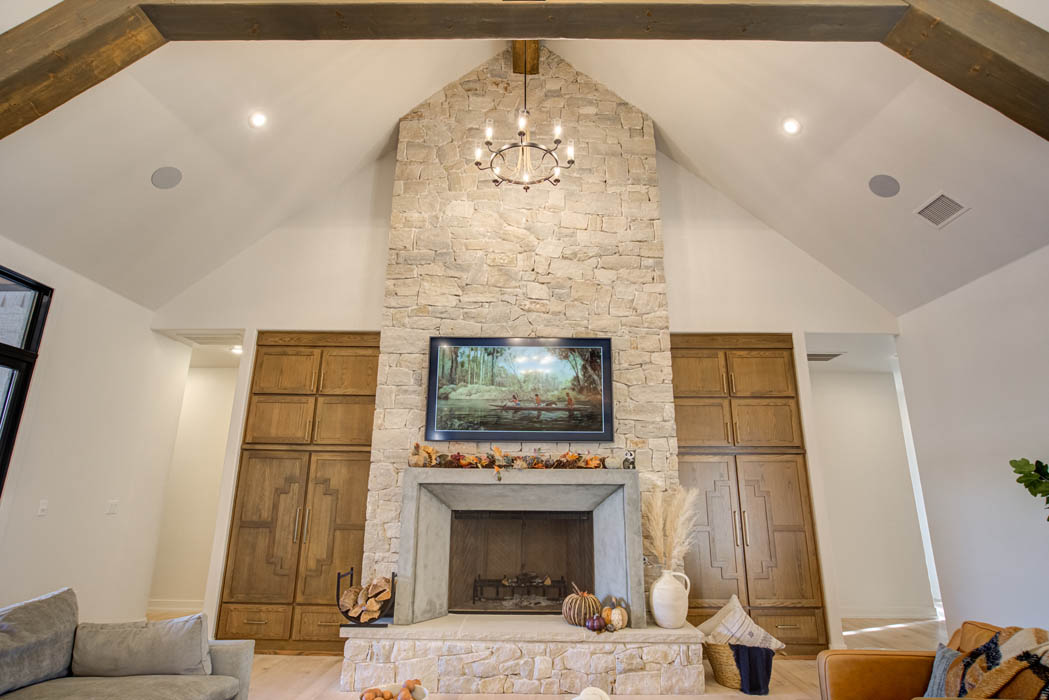 Beatufil spacious living area with vaulted ceiling and stone fireplace, in custom home near Lubbock, Texas.