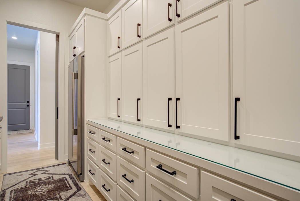 Butler's pantry behind kitchen in custom home near Lubbock, Texas.