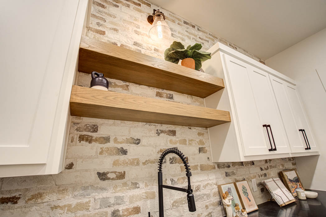 Wooden shelves in butler's pantry behind kitchen in custom home near Lubbock, Texas.