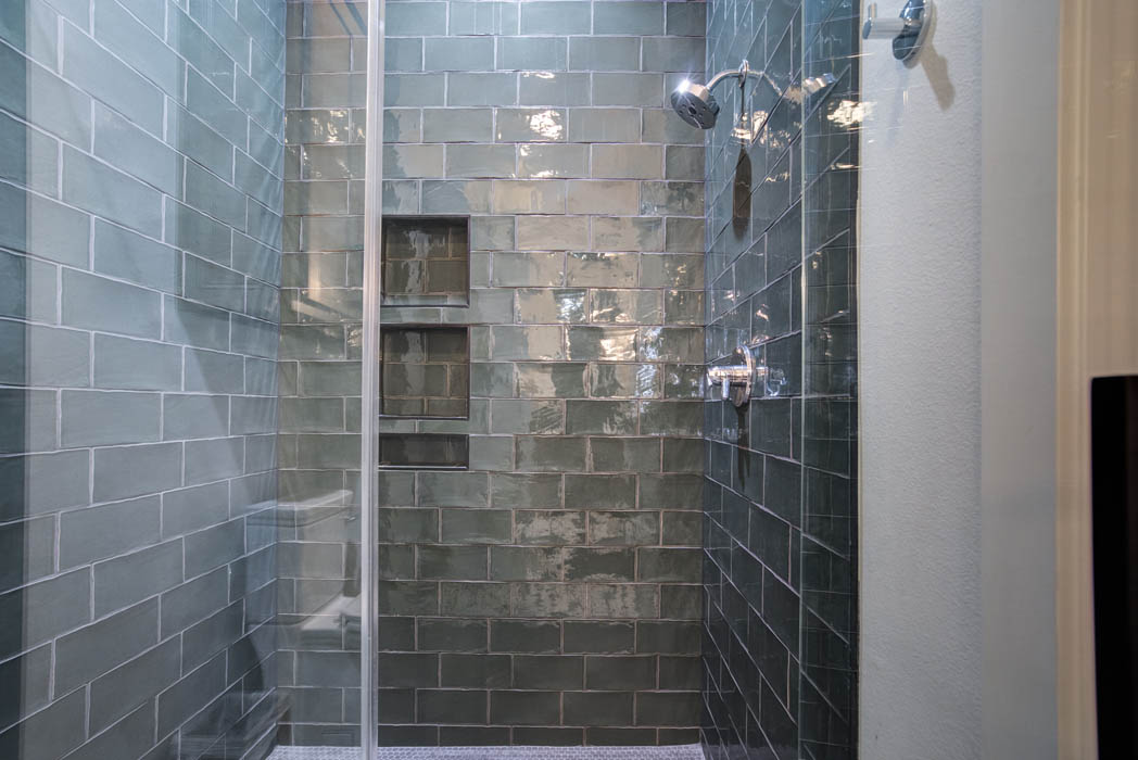 Glass shower with beautiful tile treatment in bath of custom home.