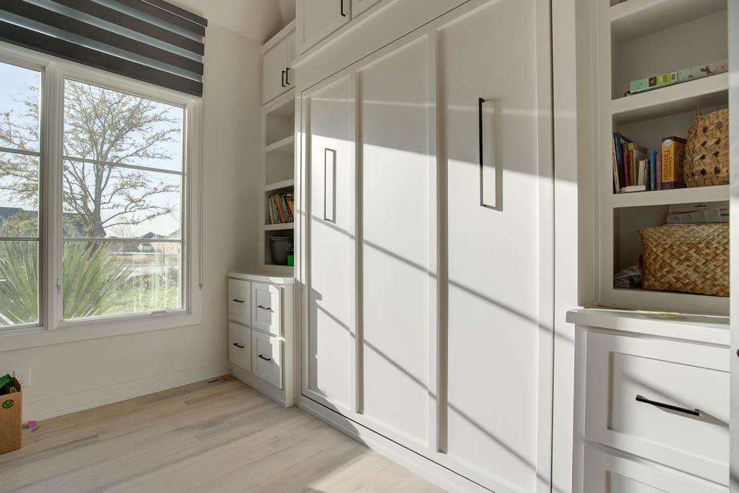 Built-in shelves in bedroom of beautiful custom home.