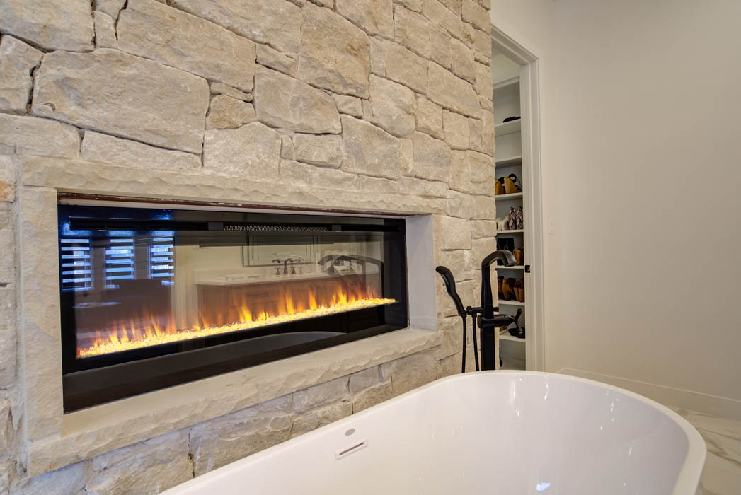 Detail of fireplace in master bath of custom home.