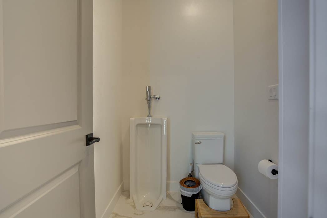 Master bath in custom home featuring separate water closet and urinal.