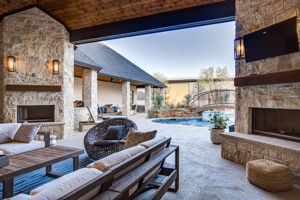 View of covered outdoor patio space in amazing backyard of custom home.