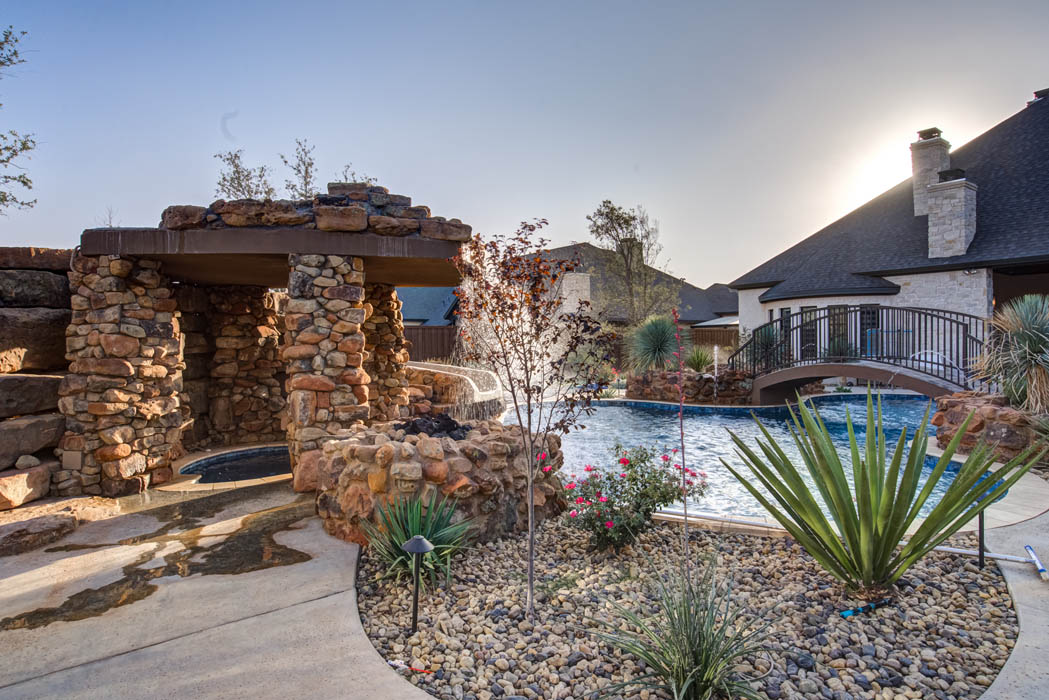 View of custom hot tub area adjacent to beautiful swimming pool and waterfall, in custom home near Lubbock.