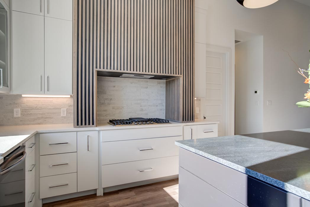 Stove and venthood area of kitchen, with custom modern design and ribbed woodwork.
