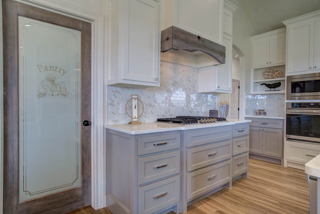 Detail of beautiful kitchen stove area with elegant pantry door, in new home for sale.