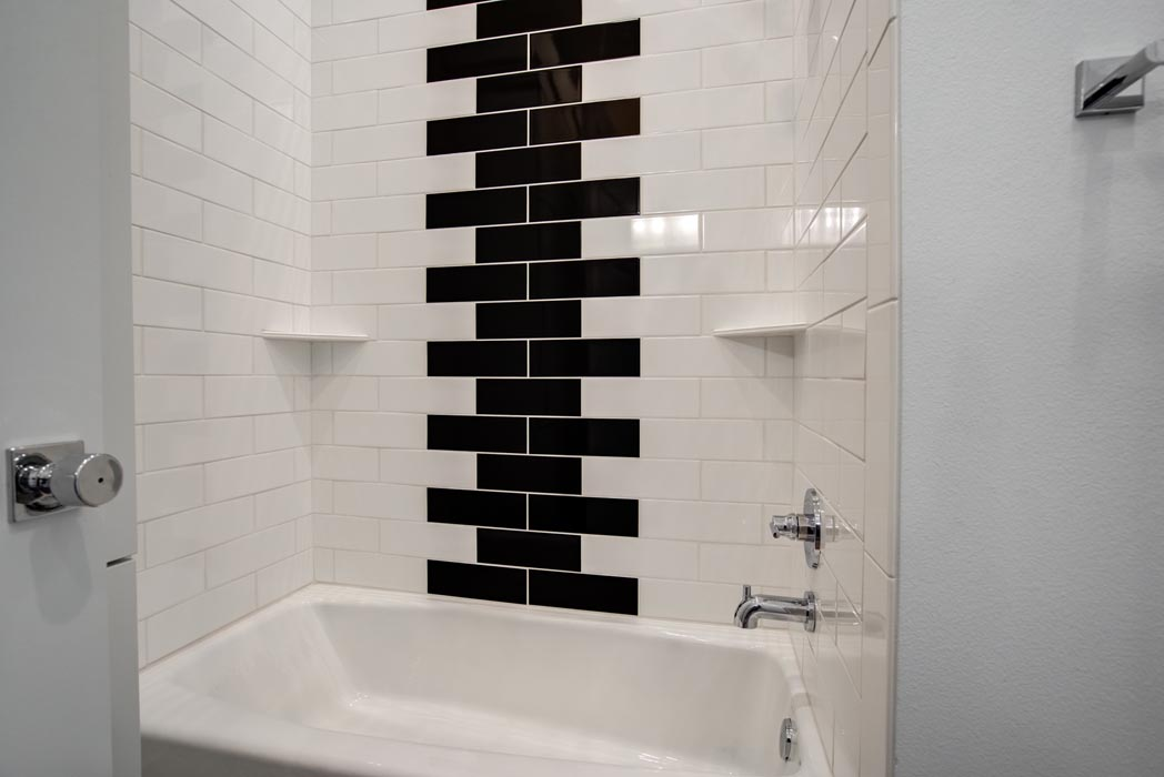 Tub shower with custom tile treatment in new custom home in Lubbock.