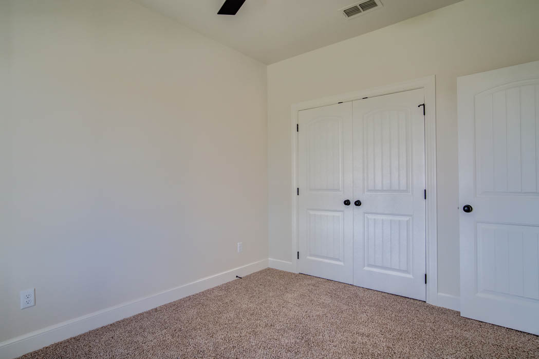 Bedroom with double closet doors in new home for sale in Lubbock.