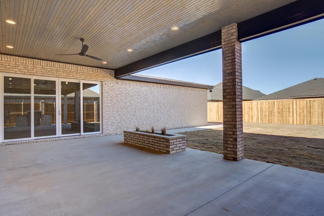 View of covered outdoor patio space in backyard of custom home.
