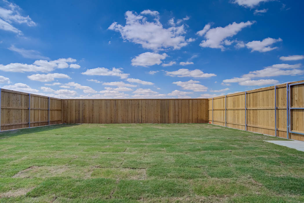 Big back yard featuring green grass in new home for sale.