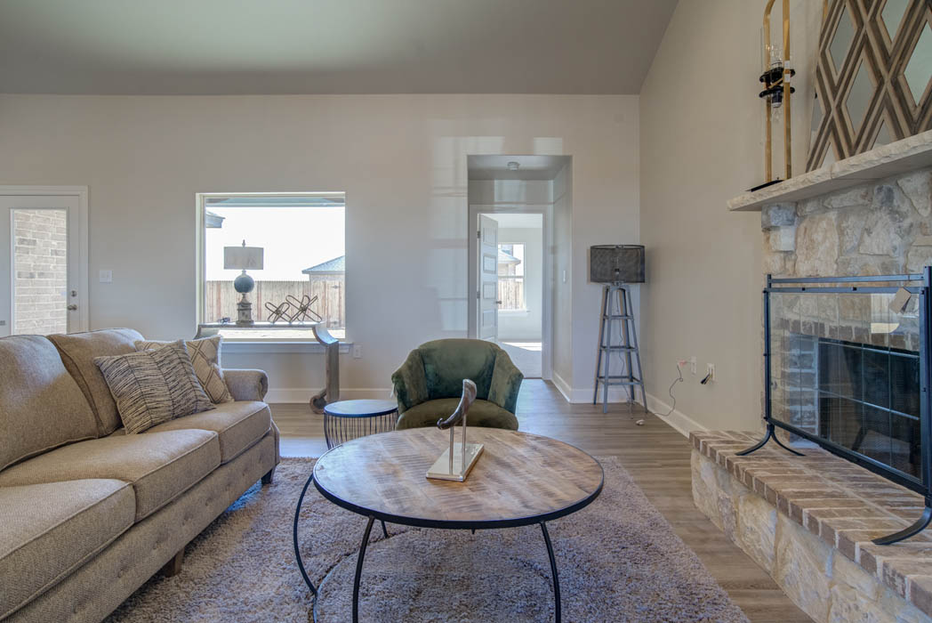 Spacious living area in Lubbock custom home featuring fireplace.