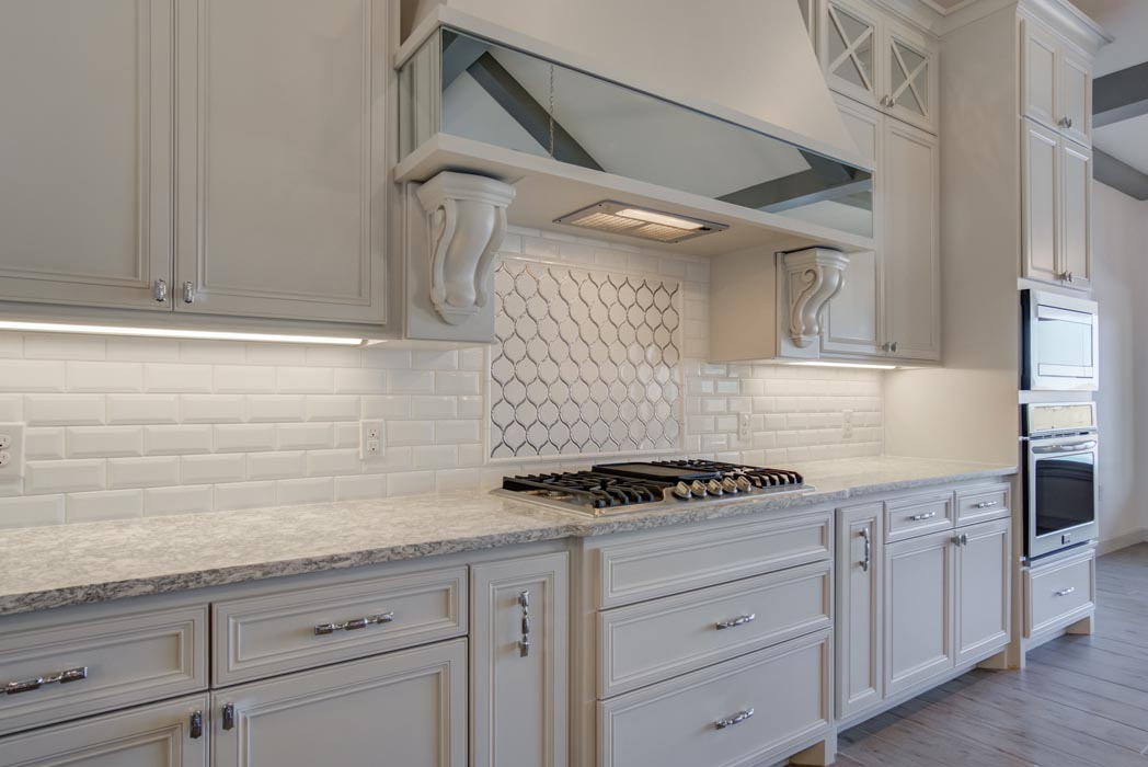 Stove and venthood area of kitchen in elegant custom home.