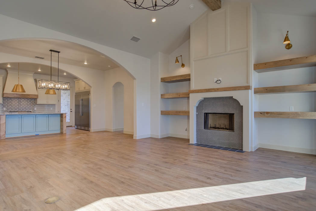 Living area in home for sale in Lubbock featuring high ceiling and fireplace.