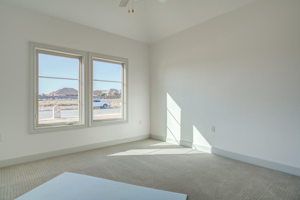 Large bedroom with ample windows in new Lubbock home.