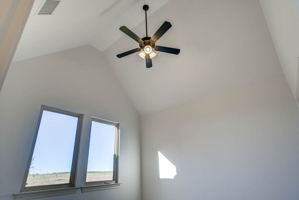Spacious bedroom in Lubbock area home for sale featuring a vaulted ceiling.