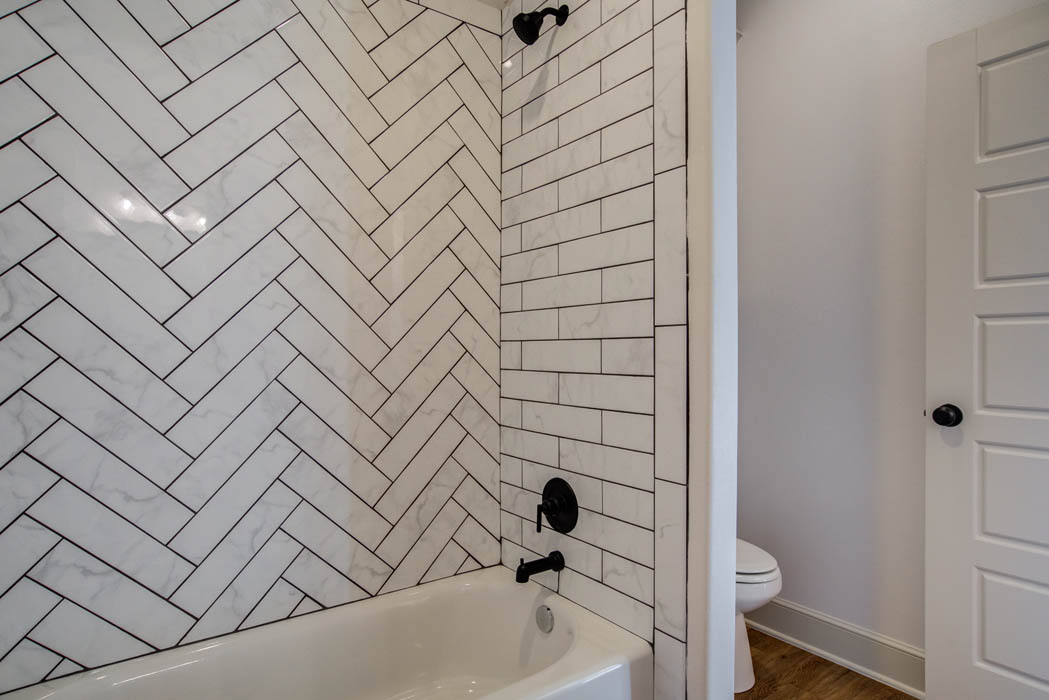 Beautiful detailed tile work in guest bath in new house for sale.