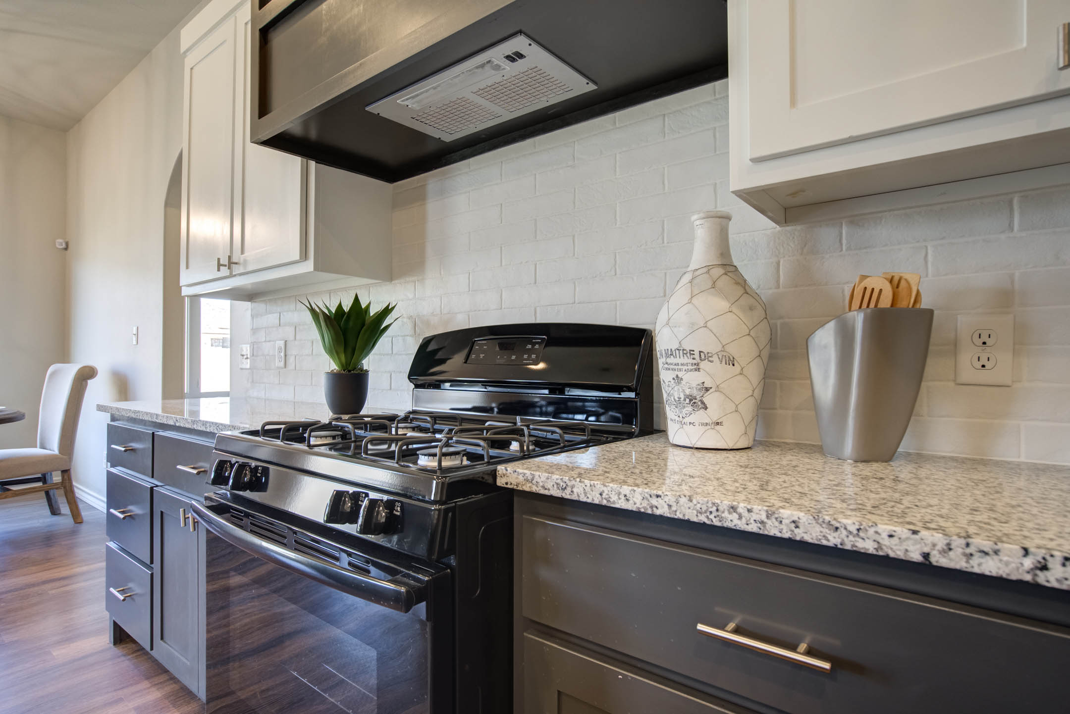 Stove area with beautiful tile treatment in kitchen of home for sale in Lubbock.