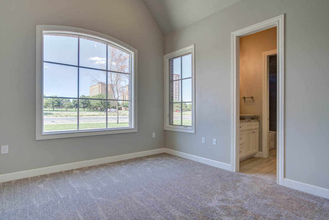Bedroom in beautiful custom home in Lubbock, with large windows.
