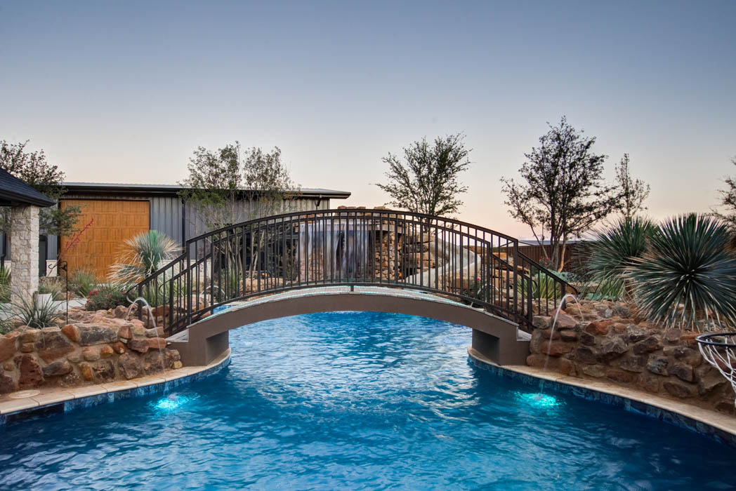 Side view of bridge over custom swimming pool in outdoor space of custom home near Lubbock.