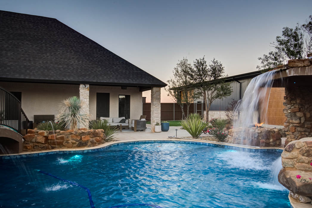 Stunning view of custom home outdoor space, with swimming pool and waterfall, near Lubbock, Texas.