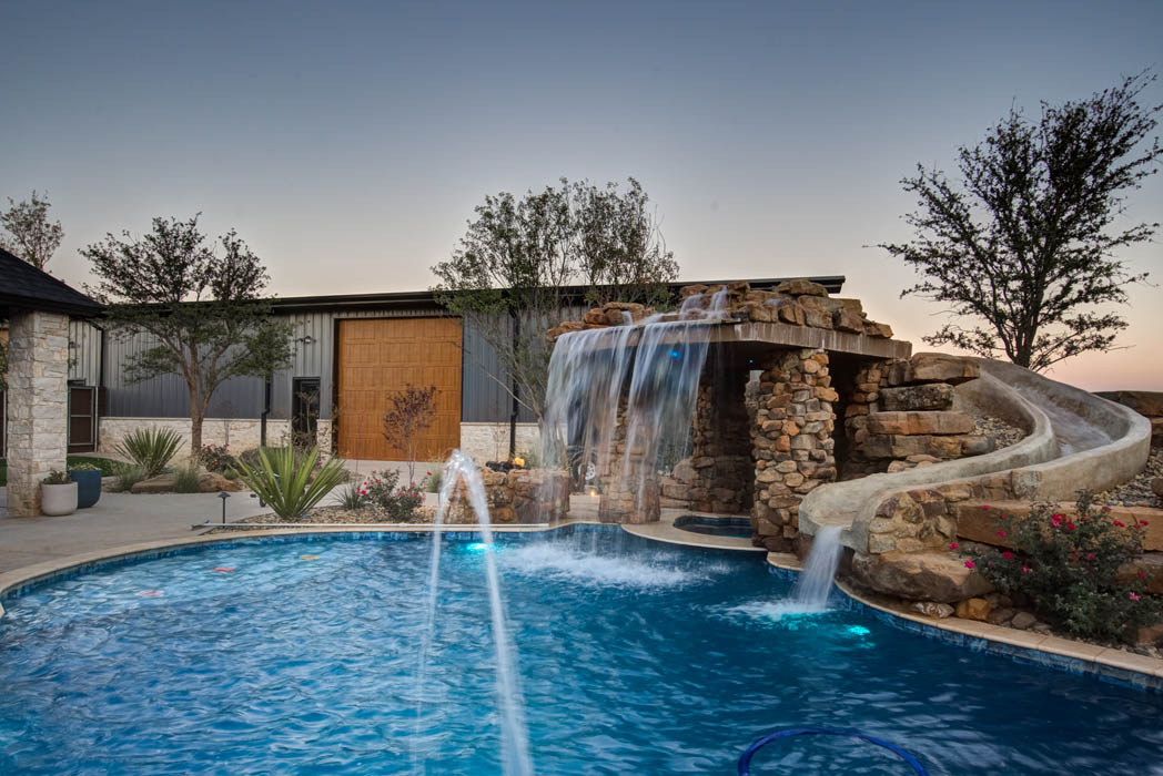 Spacious outdoor living area in custom Lubbock home featuring a pool, waterfall and bridge.