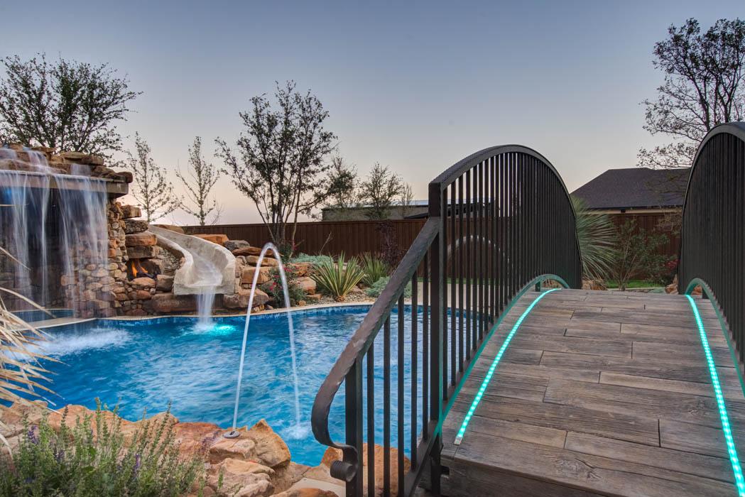 View overlooking bridge that crosses over custom swimming pool, in custom home near Lubbock.