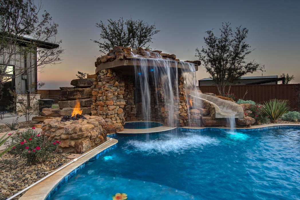 View of cascading waterfall in custom swimming pool, part of the outdoor space of a custom home built by Sharkey Custom Homes.