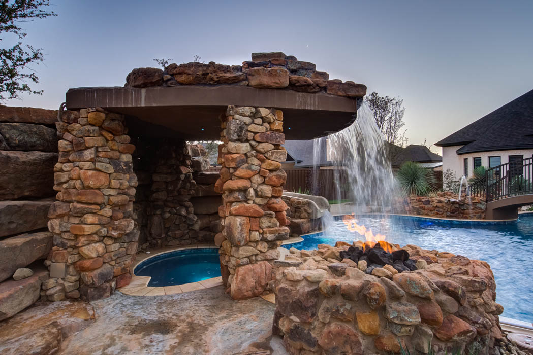 Closer view of hot tub area under swimming pool waterfall, in Lubbock area home.
