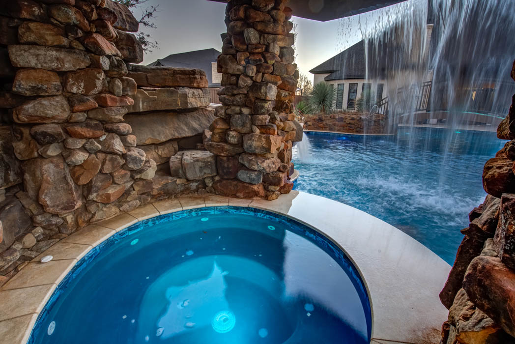 Hot tub under a waterfall, in beautiful swimming pool area of custom home.