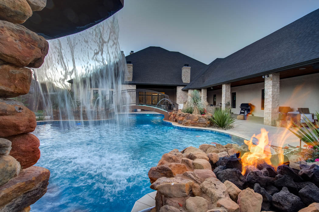 View of water plunging over waterfall in custom swimming pool in custom-built home near Lubbock.