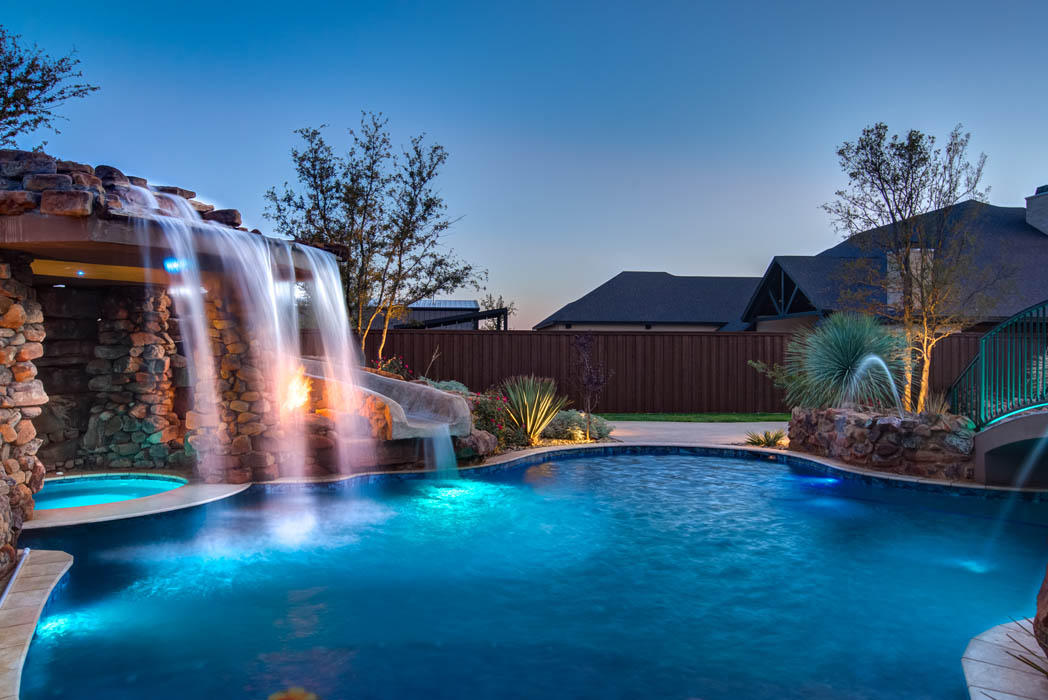 Dramatic evening lights accent plunging waterfall in custom pool of beautiful home near Lubbock.