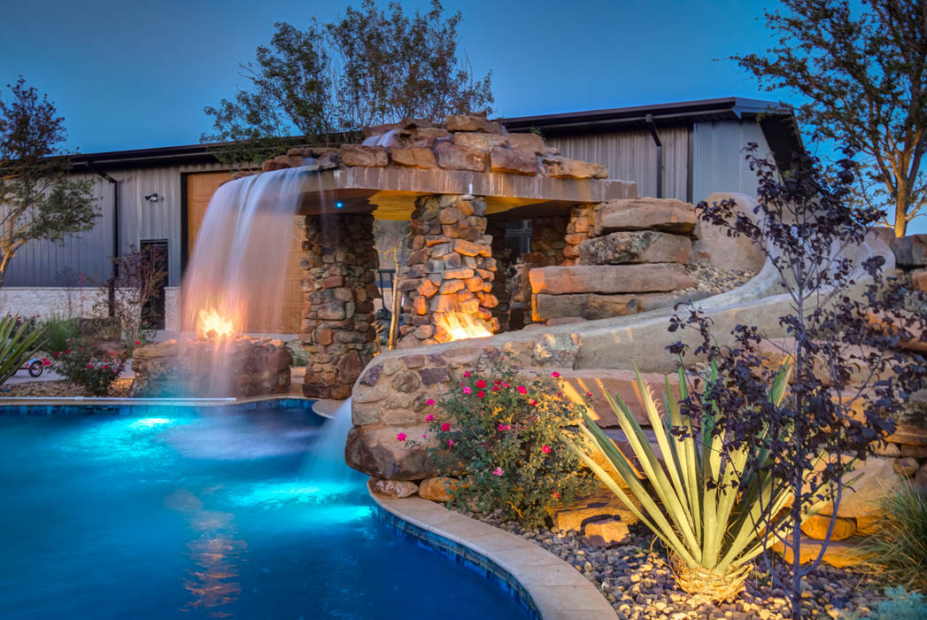 Accents lights show off beautiful swimming pool water features at night, in custom-built home near Lubbock.