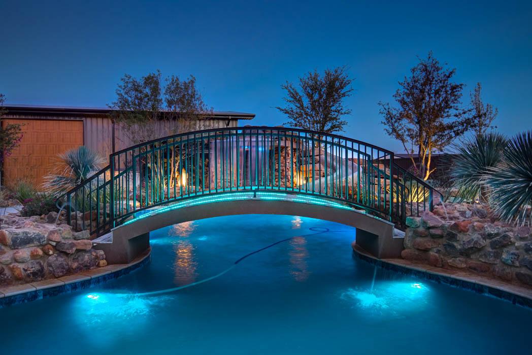 Swimming pool of custom-built home lit beautifully at night.